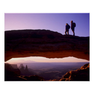 A couple watches sunrise from atop Mesa Arch in Poster