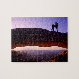 A couple watches sunrise from atop Mesa Arch in Puzzle