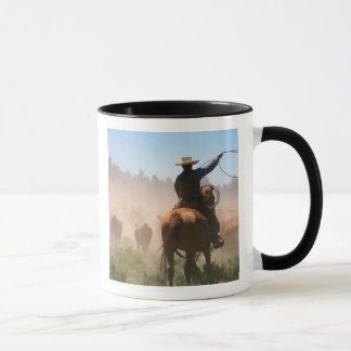 A cowboy out working the herd on a cattle mug
