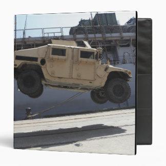A crane lifts an M998 Humvee Binder