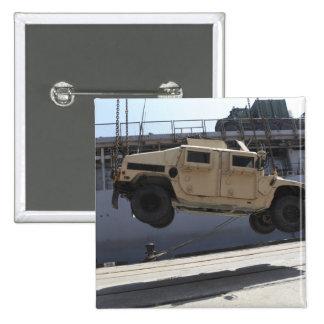 A crane lifts an M998 Humvee Button