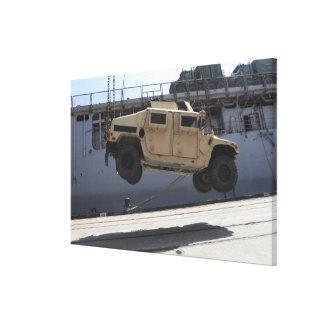 A crane lifts an M998 Humvee Canvas Print