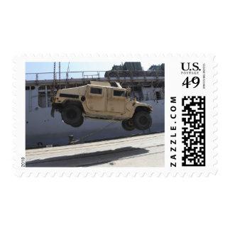 A crane lifts an M998 Humvee Postage