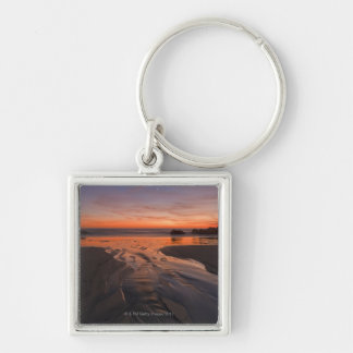 A crescent moon sets through a dusk-colored sky keychain
