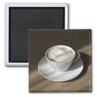 A cup of cappuccino coffee lies on an oak 2 inch square magnet