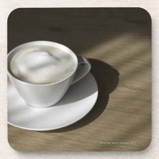 A cup of cappuccino coffee lies on an oak drink coaster