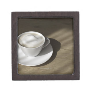 A cup of cappuccino coffee lies on an oak jewelry box