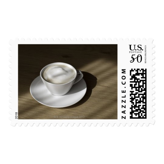 A cup of cappuccino coffee lies on an oak postage