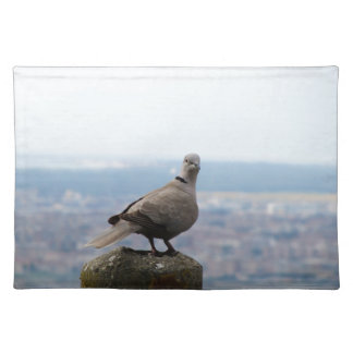 A curious collared dove on top of the world cloth place mat