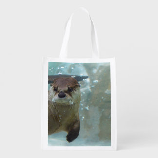 A cute Brown otter swimming in a clear blue pool Market Tote
