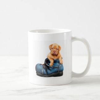 A cute little brown puppy posing over a blue shoe coffee mug