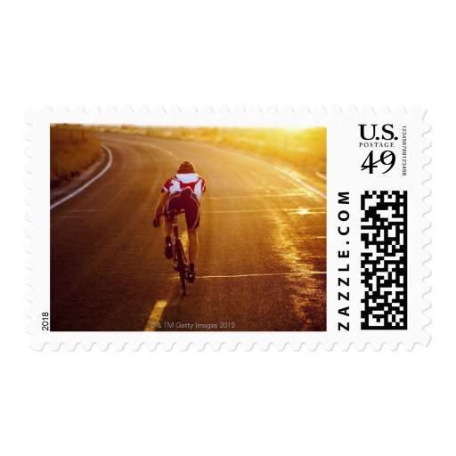 A cyclist on road bike near Great Salt Lake Postage Stamp