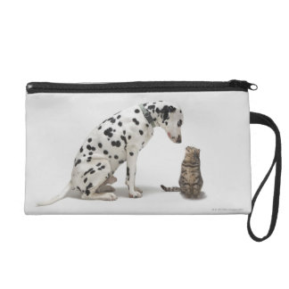 A dog looking at a cat wristlet purse