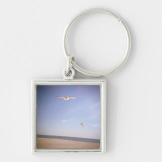 a dreamy image of seagulls flying at the beach keychain