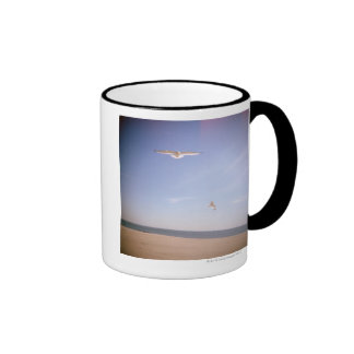 a dreamy image of seagulls flying at the beach ringer mug