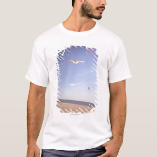 a dreamy image of seagulls flying at the beach T-Shirt