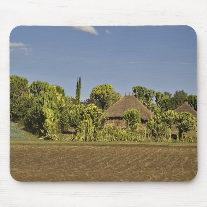 A farmed field in front of thatched roof houses mouse pad
