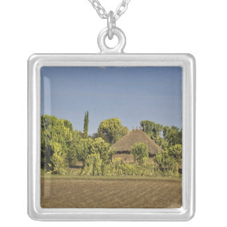 A farmed field in front of thatched roof houses square pendant necklace