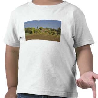 A farmed field in front of thatched roof houses tee shirt
