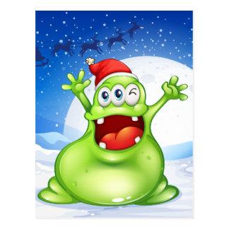 A fat green monster wearing a red Santa hat Postcard