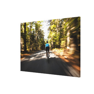 A female cyclist quickly rides on a small narrow canvas print