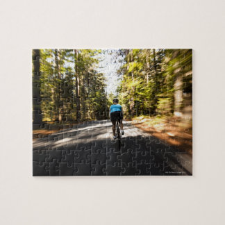 A female cyclist quickly rides on a small narrow jigsaw puzzle