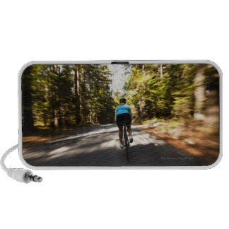 A female cyclist quickly rides on a small narrow mini speaker