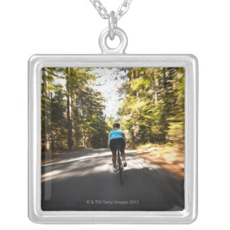 A female cyclist quickly rides on a small narrow square pendant necklace