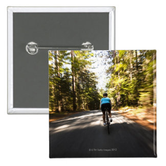 A female cyclist quickly rides on a small narrow pinback button