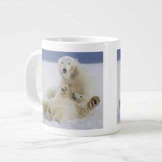 A female polar bear and her cub play in the snow giant coffee mug