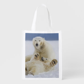 A female polar bear and her cub play in the snow reusable grocery bag