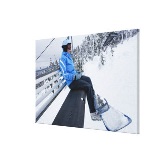 A female snowboarder rides the chair lift in New Canvas Print