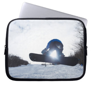 A female snowboarder takes air in New Hampshire. Computer Sleeves