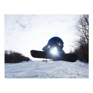 A female snowboarder takes air in New Hampshire. Postcard