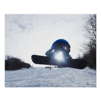A female snowboarder takes air in New Hampshire. Poster