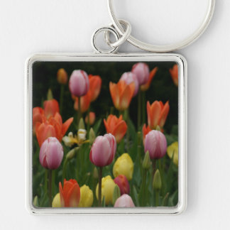 A field of peonies, cyclamens and tulips flowers keychain