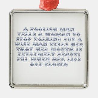 A foolish man tells a woman to stop talking, metal ornament