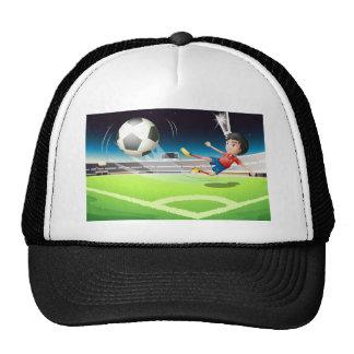 A football player kicking a ball trucker hat