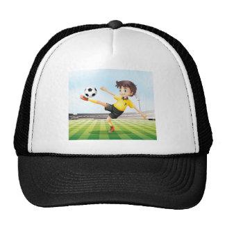 A football player kicking the ball trucker hat