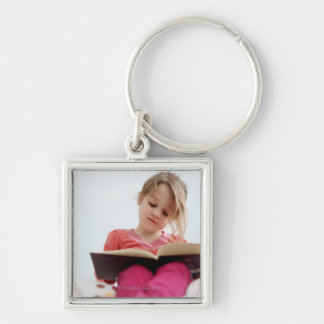 A four-year-old girl reads a book while sitting keychain