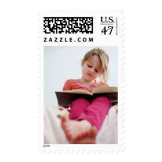 A four-year-old girl reads a book while sitting postage
