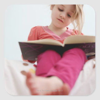 A four-year-old girl reads a book while sitting square sticker