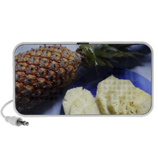 A Fresh whole Pineapple and slices on a plate iPhone Speakers