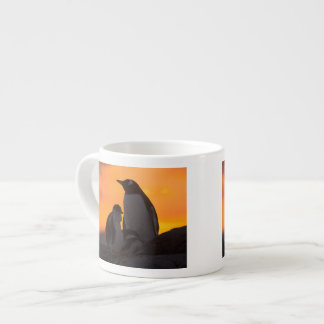 A gentoo penguin adult and chick are silhouetted espresso cup