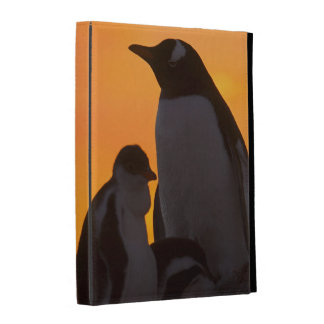 A gentoo penguin adult and chick are silhouetted iPad folio case