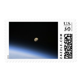 A gibbous moon visible above Earth's atmosphere 2 Postage