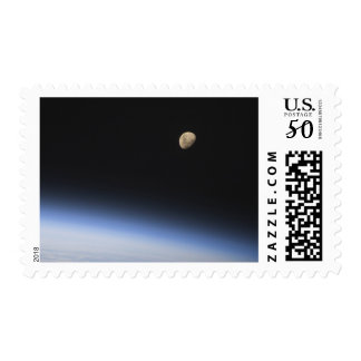 A gibbous moon visible above Earth's atmosphere Postage