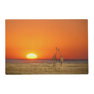 A Giraffe couple walks into the sunset, in Placemat
