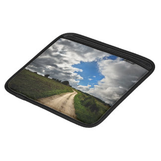 A Green Field With A Road In The Middle Of It And iPad Sleeve