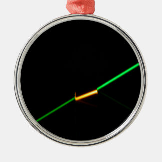 A green laser penetrating a dark colored glass. metal ornament